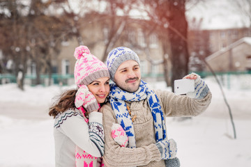 couple in love making selfie on winter picnic at park.