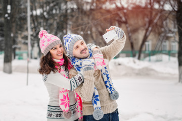 couple in love making selfie on winter outdoors in sweaters, scarf and mittens