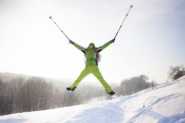 Girl in winter clothes jumping up.