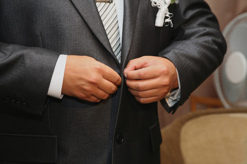 groom buttoning the buttons on the suit