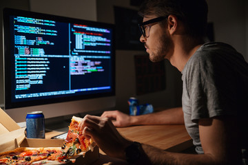 Concentrated software developer eating pizza and coding