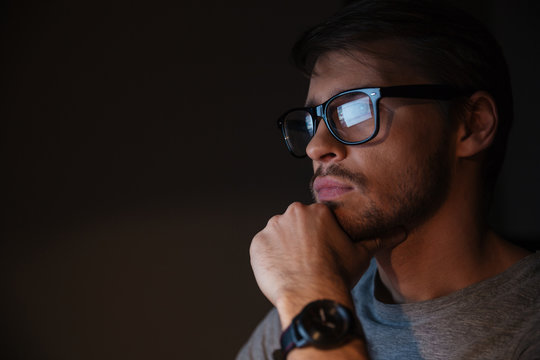 Closeup of focused man in glasses looking at screen