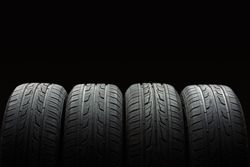 new tires are close to each other on an isolated dark background