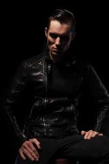 man in black leather jacket posing seated in dark studio
