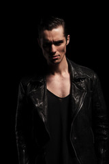 latin biker in black leather jacket posing in dark studio