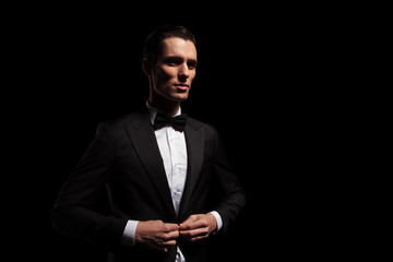 model in black tux with bowtie posing in dark studio