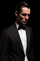 classy man in tuxedo looking away in dark studio