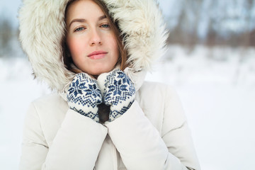 Christmas girl outdoor portrait. Woman in winter clothes on a snow field.