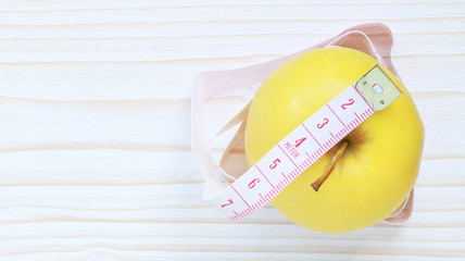 Fresh yellow apple and measuring tape