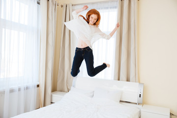 Cheerful woman jumping on the bed