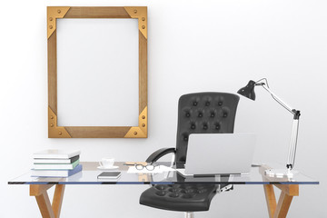 Work desk with a laptop and a blank picture frame on the wall, m