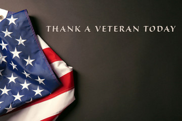 Text Thank A Veteran Today on black background near American flag