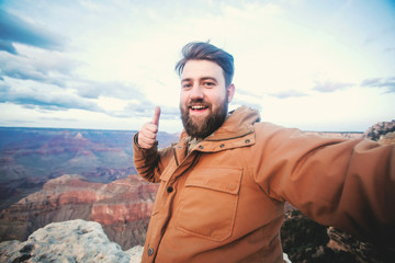 Travel hiking selfie photo of handsome bearded man student at Grand Canyon viewpoint in Arizona, USA