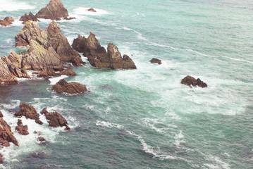 Loiba Cliffs. Waves and stones at sea.