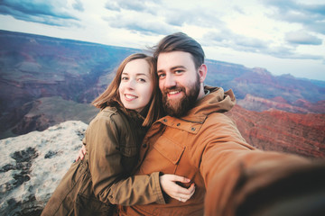 Romantic couple or friends show thumbs up and make selfie photo on travel hiking at Grand Canyon viewpoint in Arizona, USA