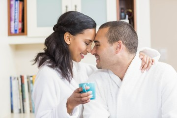 Smiling couple embracing in bath robe