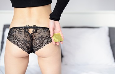 Rear view of young sexy woman holding a golden condom