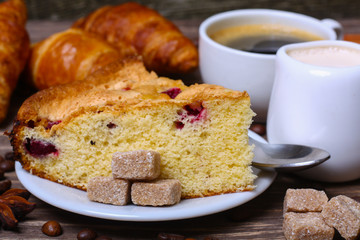 cup of coffee with cake with cranberries and croissants on a wooden background