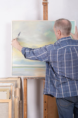 An artist painting with a palette knife in his studio