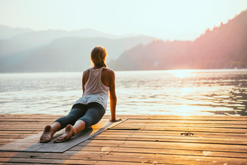 Photo sur Aluminium Ecole de Yoga Yoga sun salute. Young woman doing yoga by the lake at sunset