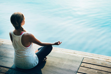 Meditation, water. Young woman meditating by the lake. Calm water surface convenient for text