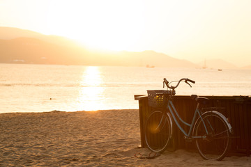 Blue bicycle standing on sandy beach