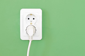 European white electrical outlet socket and white cable pluged i
