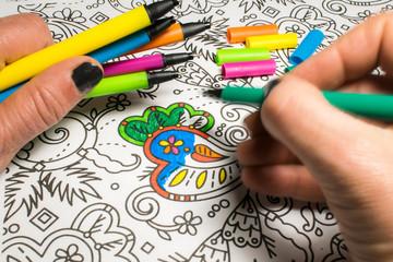 Trend für Stressabbau - Ausmalbuch für Erwachsene - Nahaufnahme einer Hand, die Stifte hält - zeichnend auf einem Blatt Papier mit Muster zum Ausmalen - Nahaufnahme