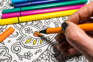 Trend für Stressabbau - Ausmalbuch für Erwachsene - Filzstifte und Hand in Nahaufnahme beim Zeichnen auf einem Blatt Papier mit Muster zum Ausmalen