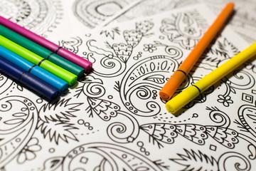 Trend für Stressabbau - Ausmalbuch für Erwachsene - Stifte in verschiedenen Farben auf einem Blatt Papier mit Muster zum Ausmalen . Nahaufnahme