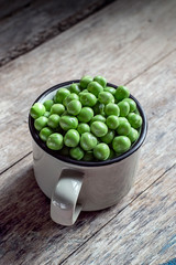 Dried green peas in a vintage mug on a wooden background. Selective focus