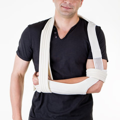 Man with Arm Supported in Sling in White Studio.