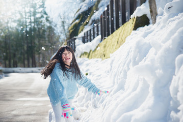 asian girl smiling outdoors in snow on cold winter day