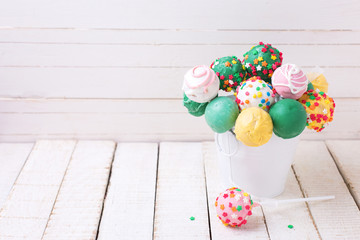 Cake pops in bucket  on white  painted wooden background.