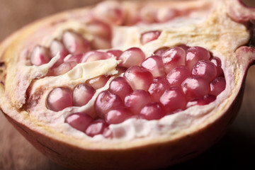 macro open pomegranate in half on wooden background