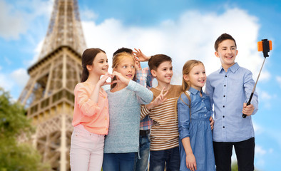 kids and smartphone selfie stick over eiffel tower