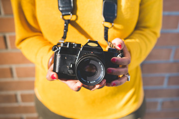 Close up on the hands of a woman holding a vintage camera - photogrpahy, creative, art concept
