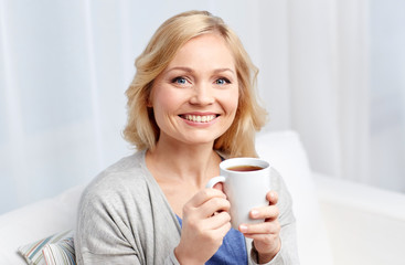 smiling woman with cup of tea or coffee at home