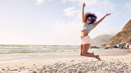 Beautiful young woman jumping at the beach Wall mural