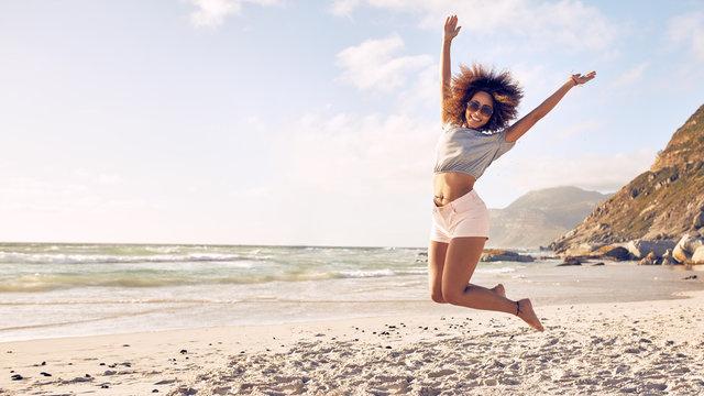 Beautiful young woman jumping at the beach