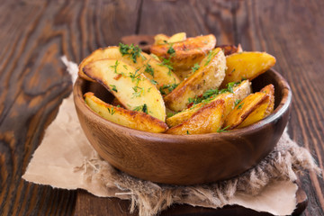 Potato wedges with dill in wooden bowl