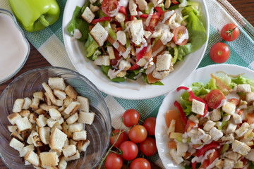 Caesar salad with croutons, dressing, chicken, cherry tomatoes top view