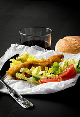 Fried fish with lettuce, lemon and tomato