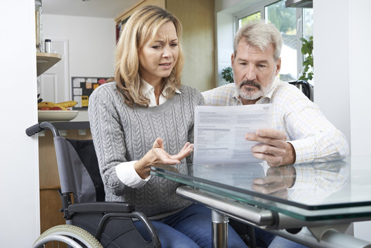 Frustrated Couple With Woman In Wheelchair Reading Letter