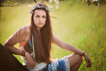 Beautiful hippie woman leaning on a tree