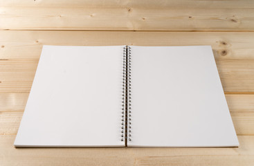 Open notebook with white lined pages on wooden office desk