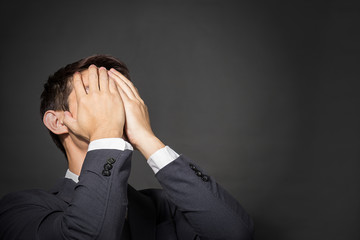 Businessman  covering his face with hand