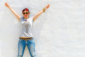 Young brunette standing on a white wall during a sunny summer da