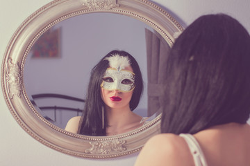 Portrait of beautiful mysterious young woman in carnival mask in front of the mirror, beauty fashion concept, dreamy filter applied