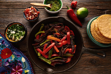 Beef fajitas in a pan with sauces Mexican food